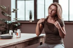 Depressed and sick woman feeling awful suffering from fever. Suffering from fever. Depressed and sick blonde-haired woman feeling awful suffering from fever royalty free stock photography