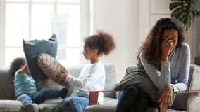 Depressed single mom tired of small noisy kids. Depressed young black mom feel upset suffering from headache tired of noisy small kids playing, upset single royalty free stock photography