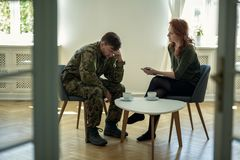 Depressed soldier and his psychotherapist during a session. View through a door stock photography