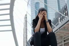 Depressed stressed young Asian business woman with hands on face sitting at outdoors. stock images