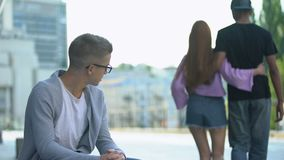 Depressed student looking at ex-girlfriend dating classmate, broken heart, pain. Stock footage stock video