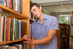 Depressed student standing at the library Stock Photo