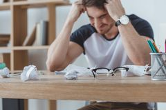 Depressed student studying at table with crumpled papers. And eyeglasses stock photography