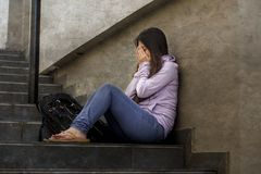 Depressed student woman or bullied teenager girl sitting outdoors on street staircase scared and anxious victim of bullying. Young sad and depressed student royalty free stock images
