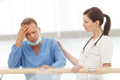 Depressed surgeon. Young female doctor comforting her depressed Stock Photography