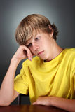 Depressed Teen. A teenaged boy sits looking depressed, his head is resting on his hand Royalty Free Stock Photo