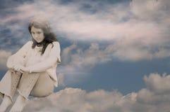 Depressed teen girl in clouds stock image