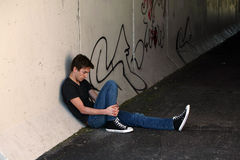 Depressed teen by graffitti Stock Images