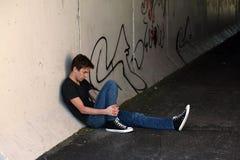 Depressed teen by graffitti