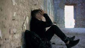Depressed teen hiding from bullying in abandoned house, difficult adolescence. Stock photo stock images