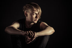 Depressed teen looking sideways over darkness. Single Caucasian teenager seated with arms around knees and looking sideways as he is surrounded by dark Royalty Free Stock Images