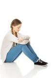 Depressed teen woman sitting. Royalty Free Stock Photo
