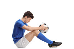 Depressed teenage football player sitting on the floor Royalty Free Stock Photos