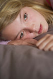 Depressed Teenage Girl Lying In Bedroom Stock Photos