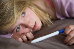 Depressed Teenage Girl Sitting In Bedroom Stock Photo