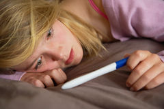 Depressed Teenage Girl Sitting In Bedroom. With Pregnancy Test royalty free stock images