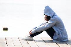 Depressed teenage girl. Sitting near river stock photos