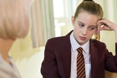 Depressed Teenage Girl Wearing School Uniform Meeting With Counselor royalty free stock images