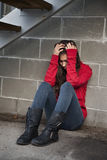 Depressed Teenager. Teenage girl sitting against brick wall in a depressed state royalty free stock photo
