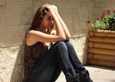 Depressed Teenager. Teenager sitting against wall with her hand on her head Stock Photo