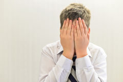 Depressed teenager boy covered his face with his hands Stock Photo