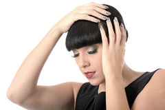Depressed Thoughtful Concerned Woman. With black hair and hispanic or european features, with eyes closed looking away from camera, and both hands on head Royalty Free Stock Image