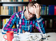 Depressed tired man holding his head. Depressed tired man in casual cloth and glasses holding his head Stock Images