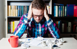 Depressed tired man holding his head. Depressed tired man in casual cloth and glasses holding his head Royalty Free Stock Image