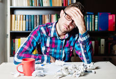 Depressed tired man holding his head. Depressed tired man in casual cloth and glasses holding his head sitting at the table Stock Photography