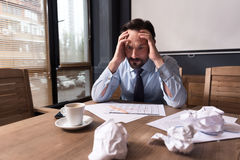 Depressed tired man holding his head. Looking for a solution. Sad depressed thoughtful man leaning at the calendar and holding his head while trying to solve the Royalty Free Stock Images