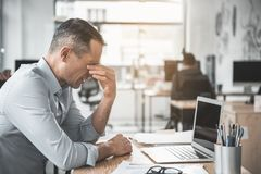 Depressed tired worker having pain in eyes. Side view unhappy weary employer rubbing eyes after long work with laptop. He situating at desk. Fatigue at job Royalty Free Stock Photography