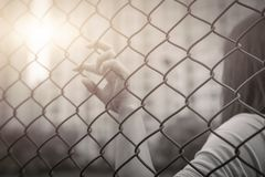 Depressed, trouble, help and chance. Hopeless women raise hand on chain-link fence ask for help. Depressed, trouble, help and chance. Hopeless woman raise hand Royalty Free Stock Photos