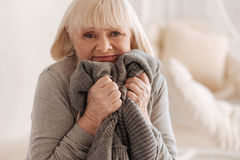 Depressed unhappy woman trying to hold tears. It is so difficult. Depressed unhappy senior woman holding a knitted jacket of her deceased husband and pressing it Royalty Free Stock Photography