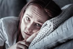 Depressed unhappy woman weeping on pillow. Expressing emotions. Sad appealing miserable woman gazing up while lying on pillow and missing him Stock Image