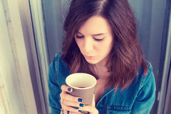 Depressed unhappy young woman sitting on stairs outdoors with coffee stock photo