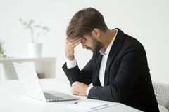 Depressed businessman shocked by bankruptcy failure sitting at w. Depressed unsuccessful businessman feels terrible headache, distraught stressed entrepreneur Royalty Free Stock Photography