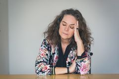 Depressed or unwell pretty middle-aged woman. Seated at a table indoors resting her head on her hand with closed eyes and a serious withdrawn expression Royalty Free Stock Image
