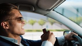 Depressed and very upset young businessman in the car. A man drinks alcohol at the wheel problems in business or. Personal life stock video