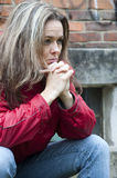 Depressed woman. Portrait of a distressed, depressed woman in a red jacket against a brick wall stock images