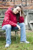 Depressed woman. Portrait of a young distressed depressed woman sitting on a bench in front of desolate graffiti house wall royalty free stock image