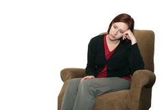 Depressed Woman. A woman sits in a chair looking sad and depressed. There is room to the left of the subject for text Royalty Free Stock Photography
