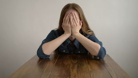 Depressed woman crying at a wooden table stock footage