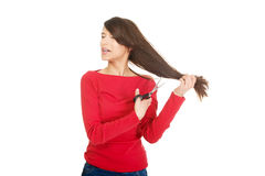 Depressed woman cutting her hair. Royalty Free Stock Photo