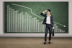 Depressed woman and declining graph. Full length of young businesswoman looks depressed and standing in front of declining financial graph Stock Image