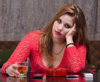 Depressed woman drinking alcohol Stock Images