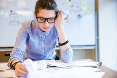 Depressed woman fashion designer drawing sketches on workplace Stock Photo
