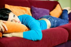 Depressed woman feeling sick at home laying on sofa Royalty Free Stock Photography