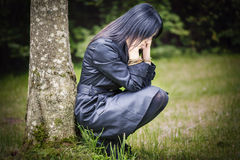 Depressed woman in focus near tree Stock Photos