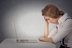 Depressed woman in front of laptop Royalty Free Stock Photos