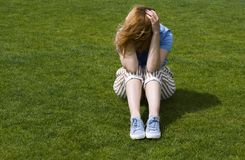Depressed woman with head in hands. Sitting on green grass stock images